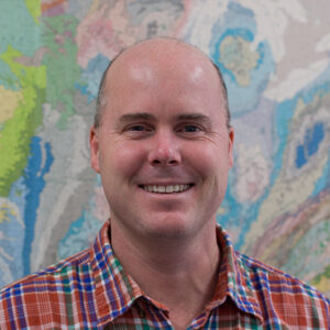 James Farquhar smiles for the camera, wearing a red and blue gingham button-up in front of a map-like abstract background.