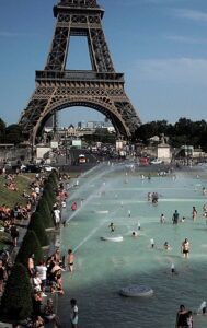 People swim in the Seine River in front of the Eiffel Tower on a hot summer day.