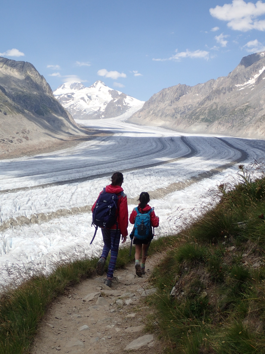 Two children walk along a path towards icy mountains
