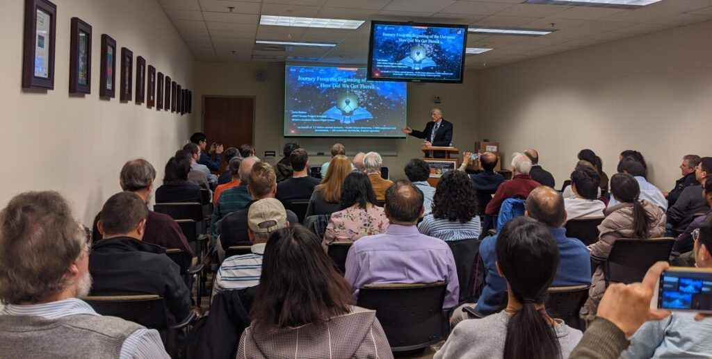 A seminar speaker presents to a large group of attendees