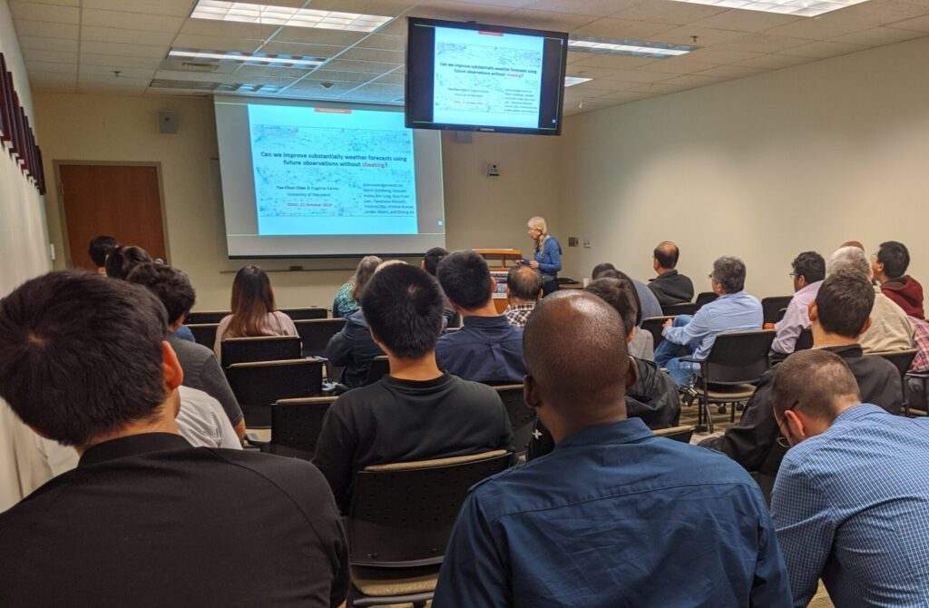 A photo of Eugenia Kalnay presenting to a packed room of participants