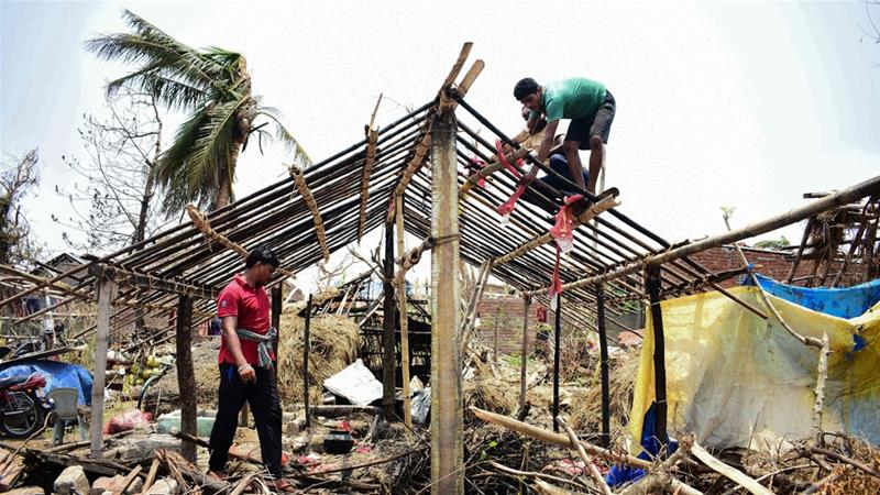 People rebuild a house out of the rubble of a ruined home