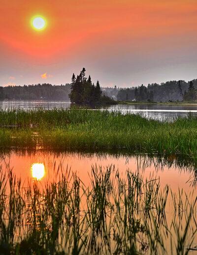 A sunset over foggy wetlands
