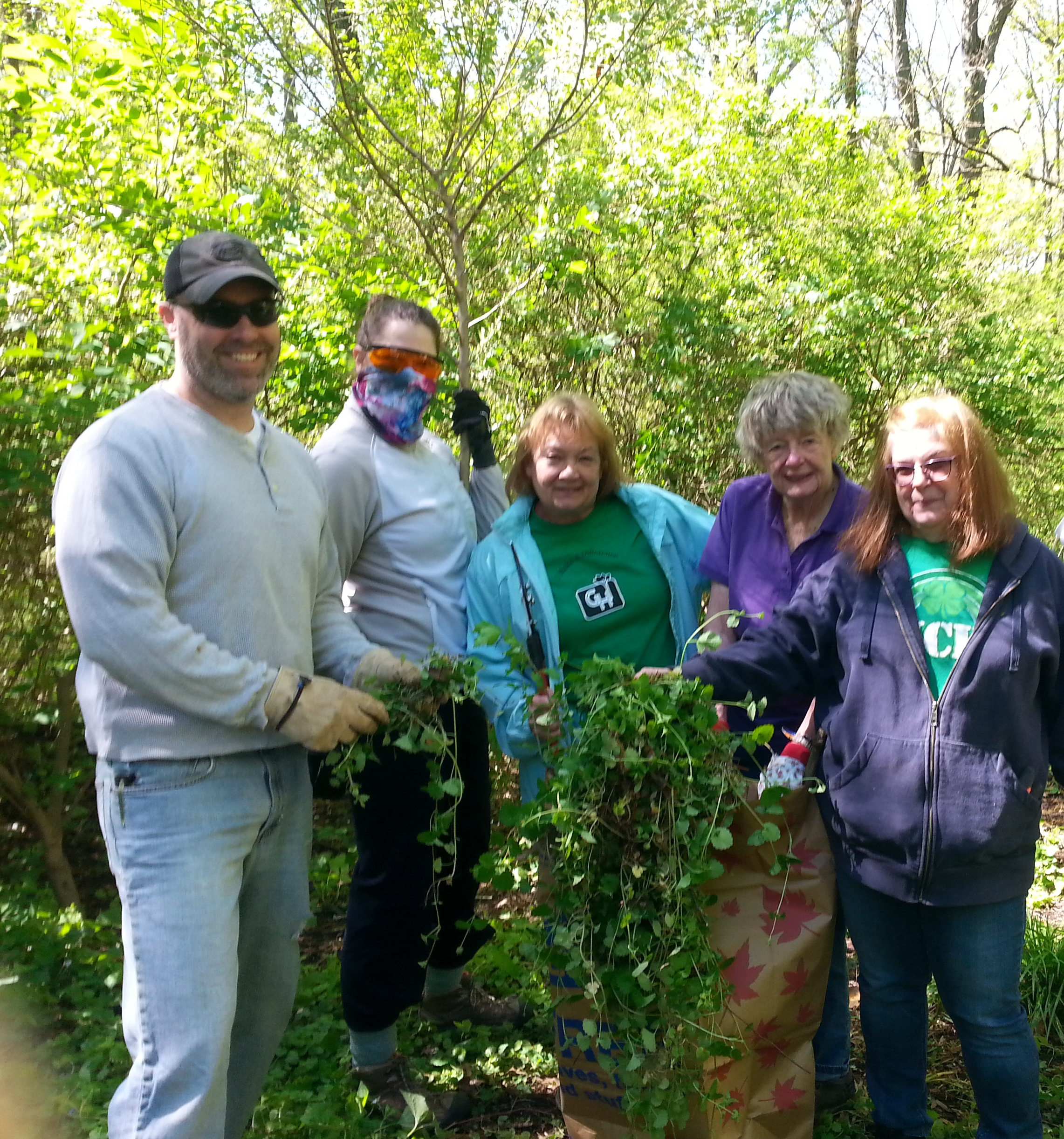 A group photo of Beth Kuser-Olsen and others as they clean up a forest