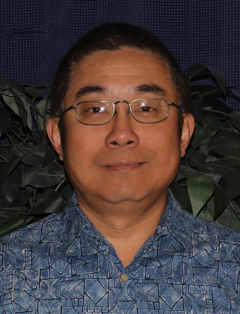 A portrait image of Gang Liu wearing a blue button-down