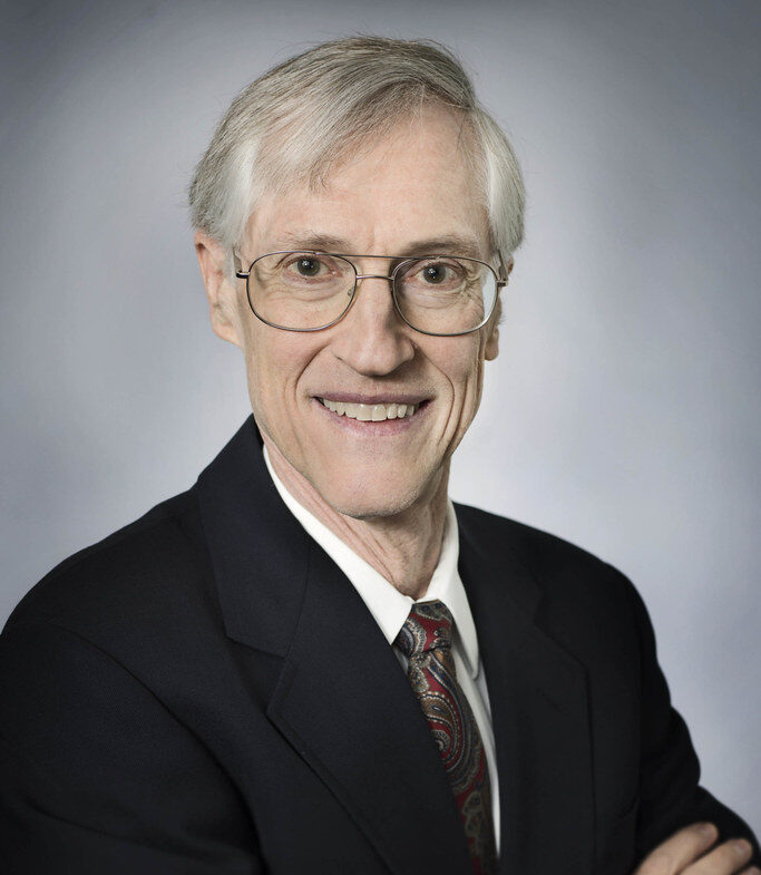 Dr. John Mather smiles warmly at the camera wearing a suit in front of a nondescript background
