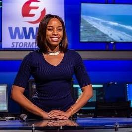 Monique Robinson, a news anchor, stands behind a desk in front of some monitors depicting the news logo