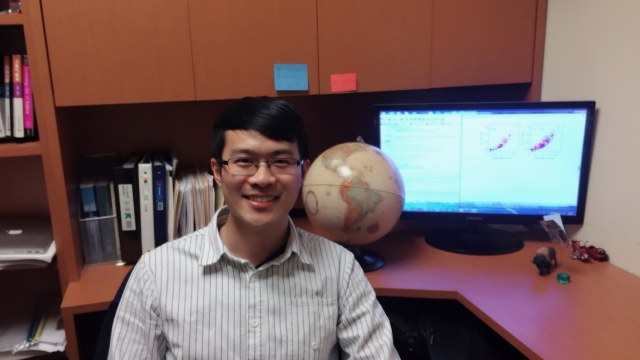 Dr. Youtong Zheng poses for the camera in front of his desk which has some books, a globe, and his computer