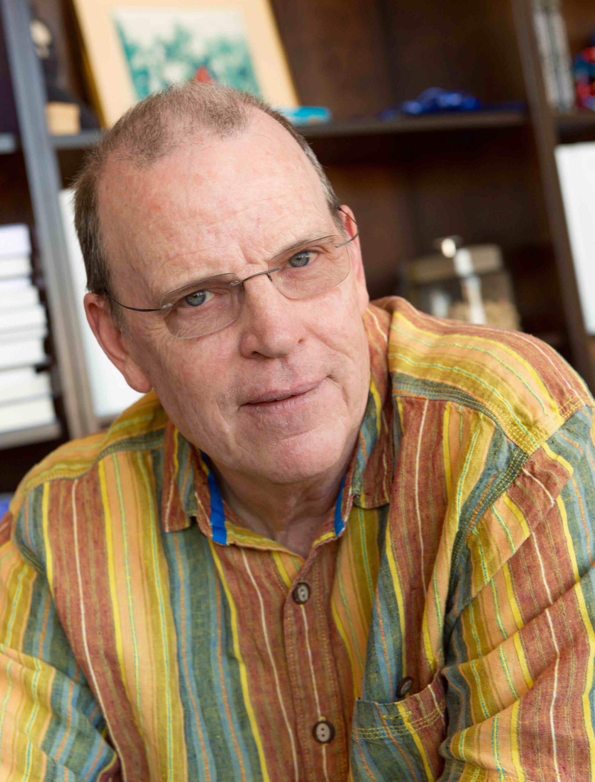 Dr. David Randall poses in front of a bookshelf wearing a colorful button-up and square glasses