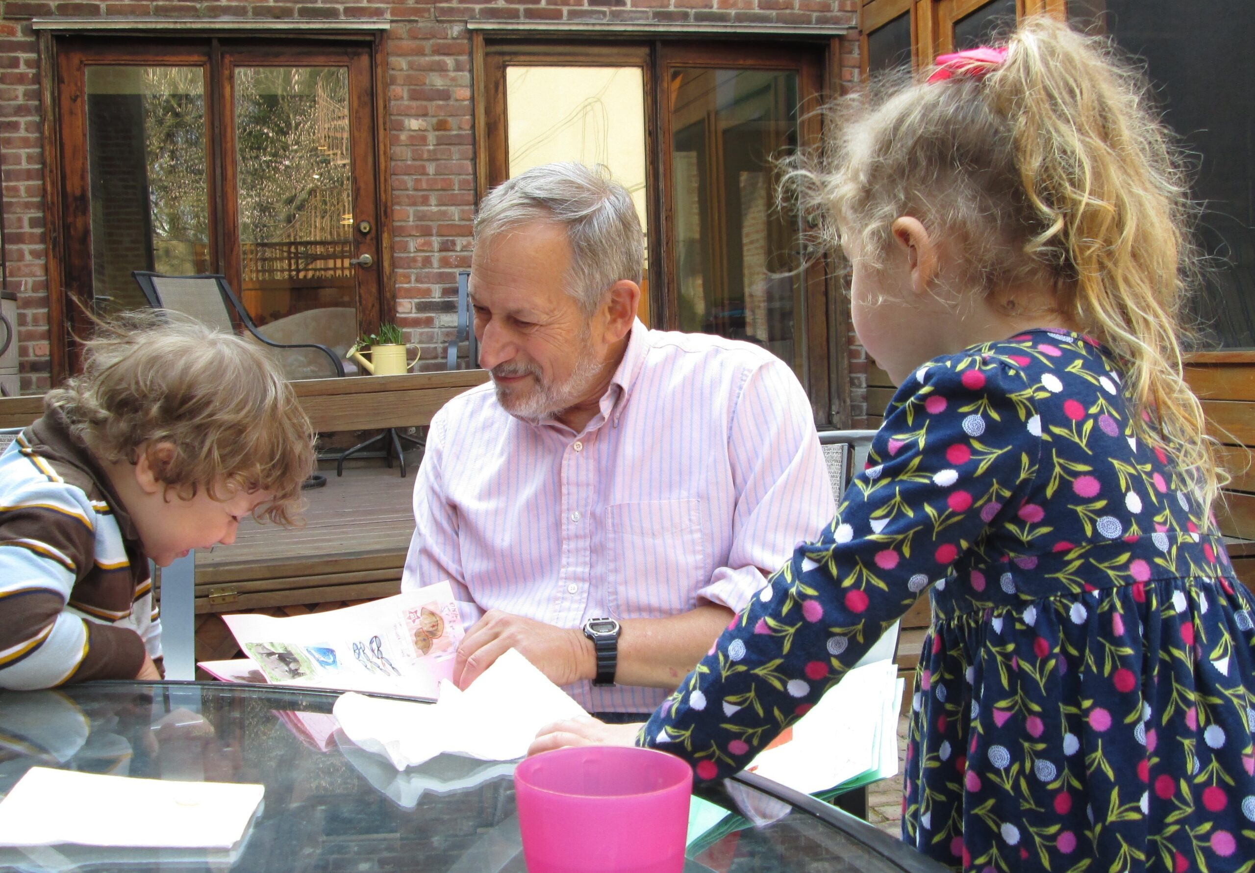 Dr. Mark Cane poses with his two grandkids as they look at some pieces of paper