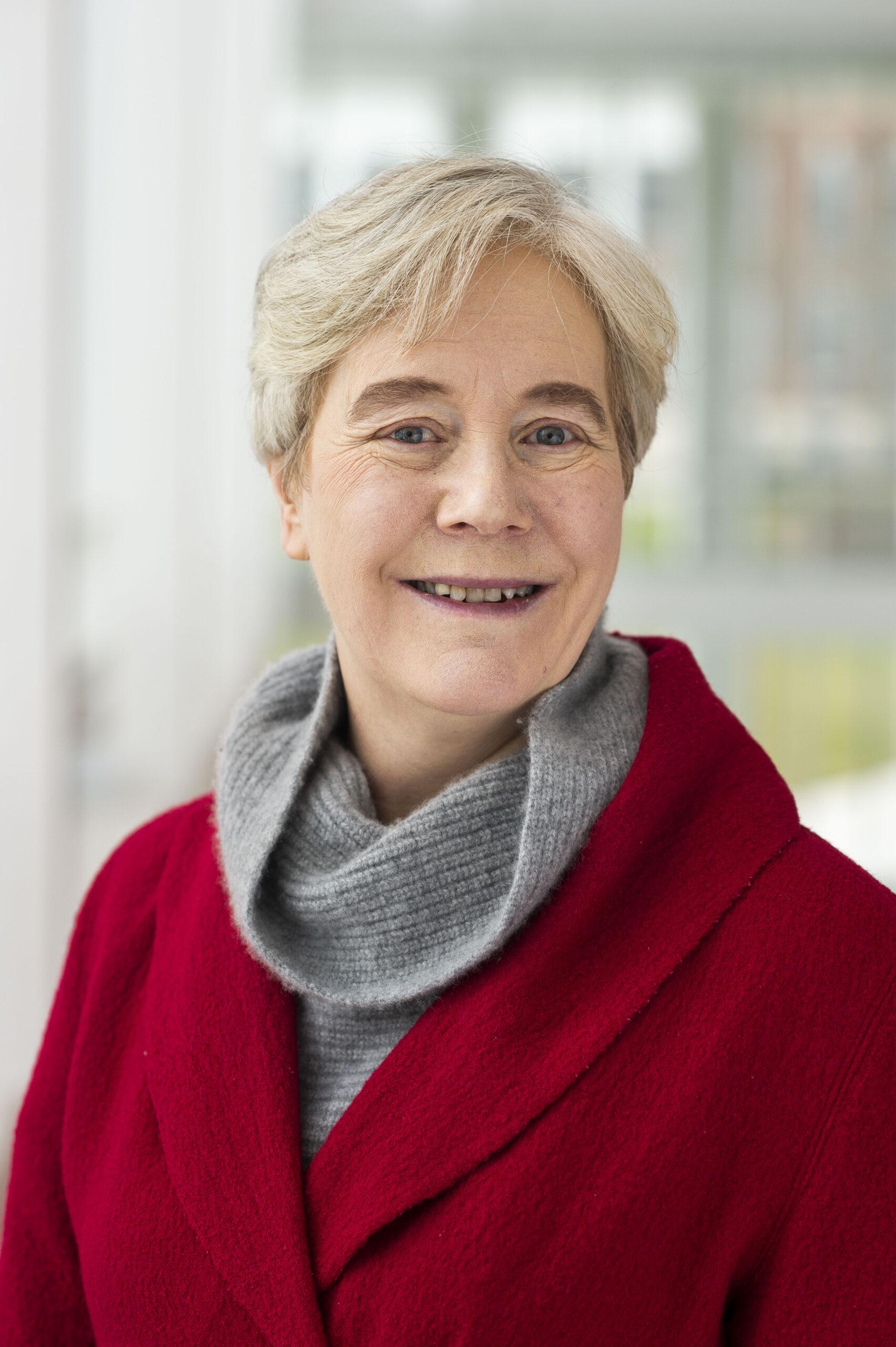 Dr. Ellen Williams smiles in a red blazer