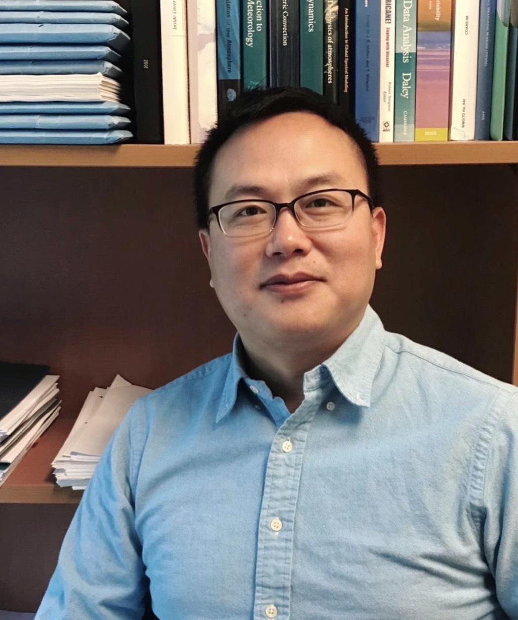 Jifu Yin poses in front of his bookshelf, wearing a blue button-down