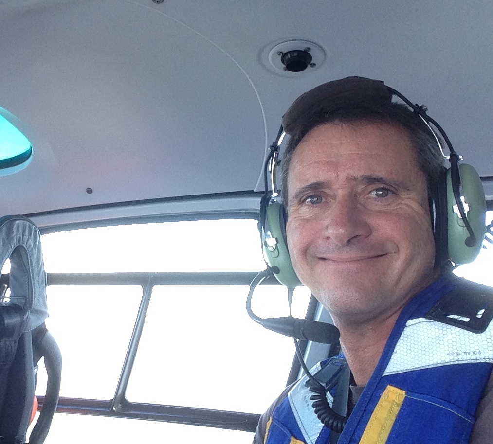 Dr. Nolan poses in a plane, wearing a headset and smiling at the camera