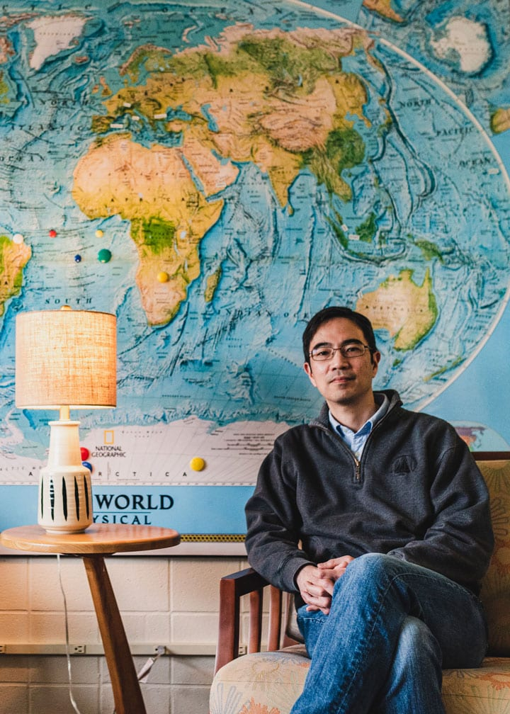 Dr. Young Oh Kwon casually sits in a chair in front of a detailed world map