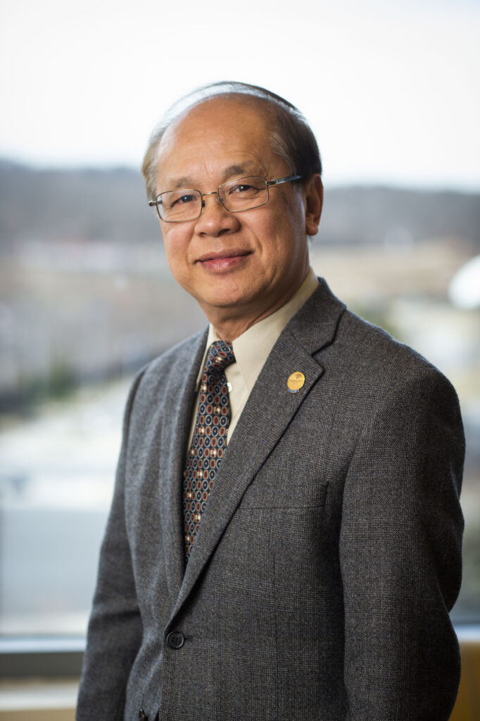 Dr. Lau, wearing a smart suit, smiles to the camera
