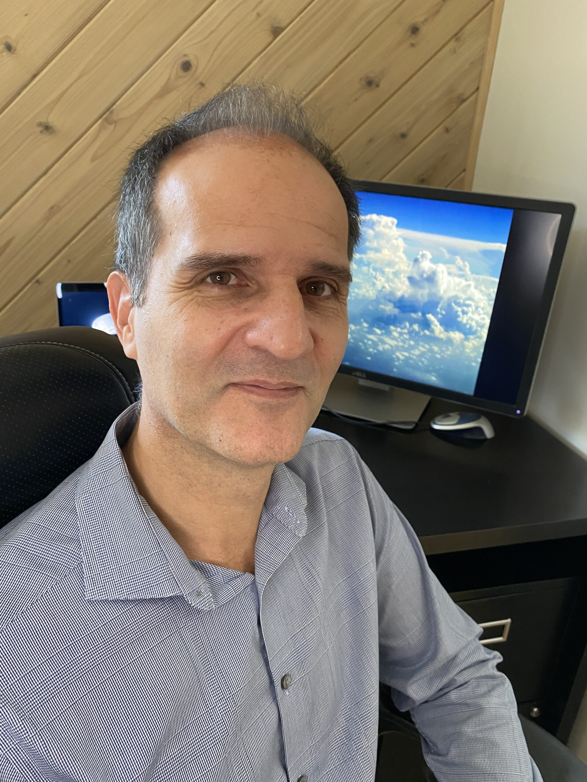 Dr. Kollias sits in his home office, smiling at the camera, and wearing a blue button-down shirt