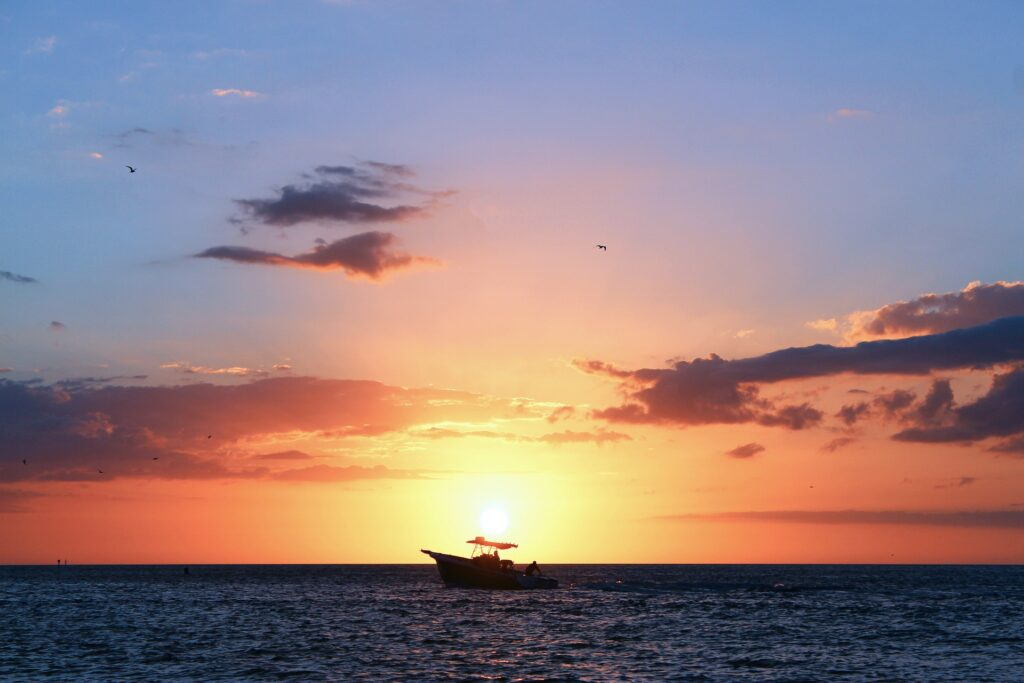 A scenic view of a boat in front of a pink sunset