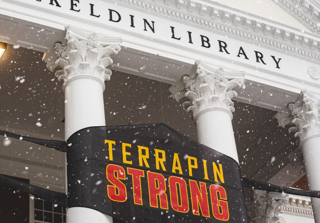 """A snowy McKeldin Library with a sign that looks like a face mask that says """"Terrapin Strong"""""""