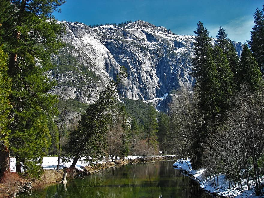 A snowy Yosemite mountain behind a lake, also surrounded by snow