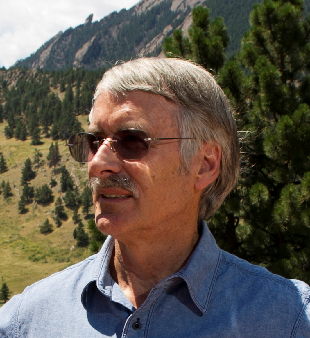Dr. Trenberth poses in front of tree-covered mountains