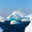 A tall iceberg melts in ocean waters