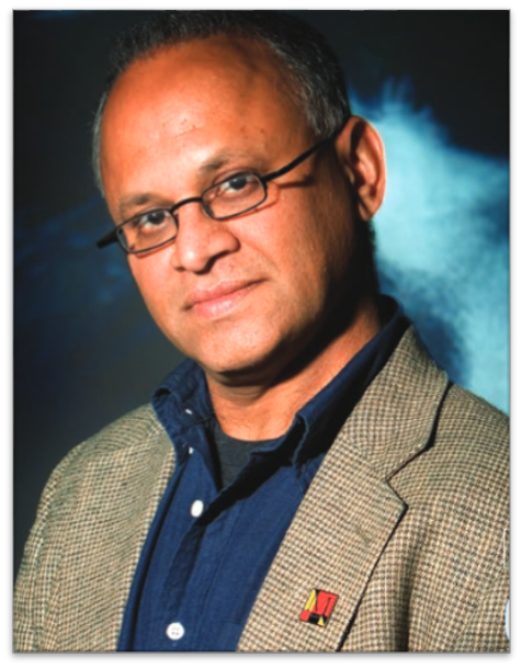 Raghu Murtugudde poses for the camera, wearing a blue button-up and a blazer