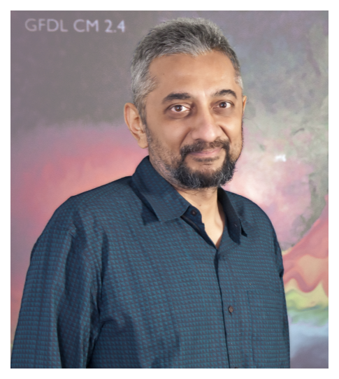 Dr. Balaji poses for a headshot, wearing a blue button-up in front of a space backdrop
