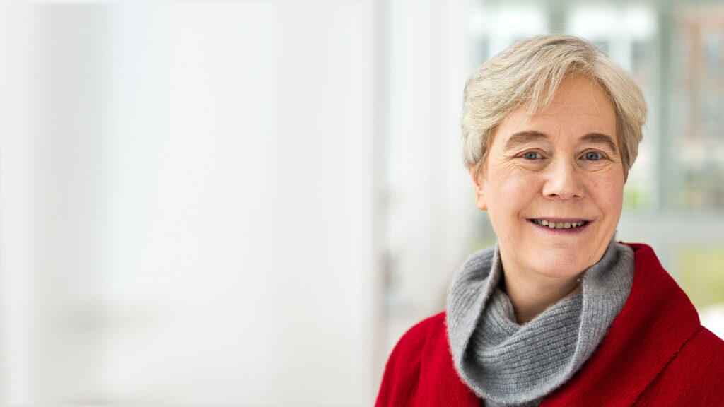Ellen Williams, wearing a red coat and a grey scarf, smiles for the camera.