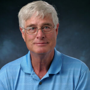 A headshot of Dr. Toon, wearing glasses and a blue polo