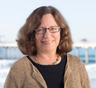 A headshot of Dr. Lynne Talley, posing in glasses and a beige cardigan.