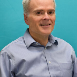 A shot of the professor smiling in front of a blue backdrop