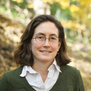 Prof. Natalie Mahowald smiles in front of a woodland backdrop, wearing a green sweater over a polo shirt.