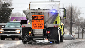 A salt truck with a caution sign on the back