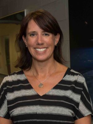 Sarah Ringerud smiles in front of a dark backdrop, wearing a striped t-shirt