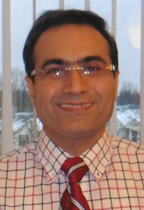 Isaac Moradi smiles for the camera, wearing a red gridded button-up and a red tie