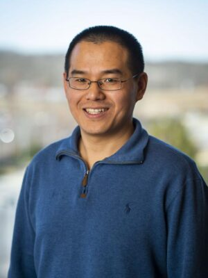 Yalei You smiles in front of a colorful backdrop, wearing a blue polo shirt