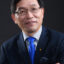 Dr. Zhanqing Li crosses his arms, wearing a suit with a blue tie.