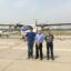 The researchers smile in front of a plane
